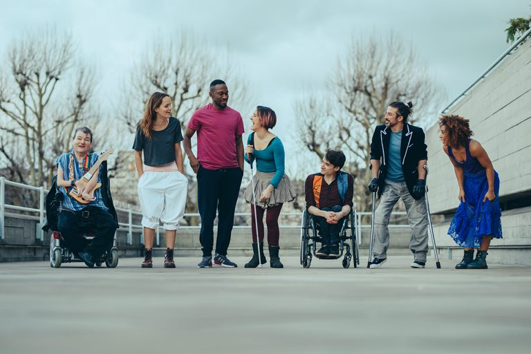 7 extraordinary artists stand in a line; left to right: a white man in a wheelchair holding a guitar, a white woman with long brown hair, a tall black man in a bright pink top, a white woman with a short bob and a walking stick, a white man in a wheelchair, a man with hair tied up holding crutches, a black woman in bold blue dress laughing.
