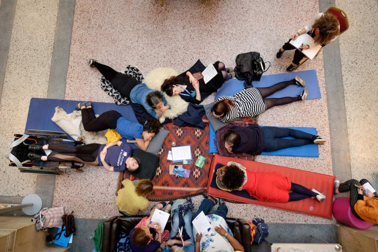 Photo from birds eye view - a group of 12 people in a circle, laying on the floor on mats and blankets, sitting on chairs and sofa. They are having a discussion; some people are taking notes on paper.