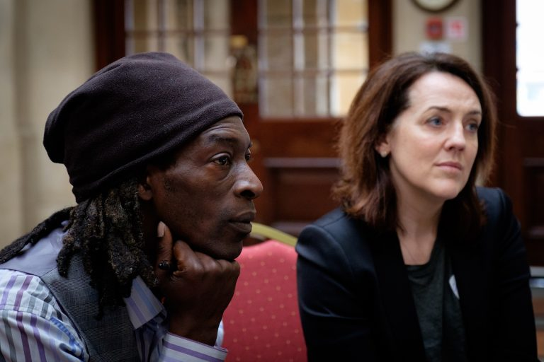 Two attendees, looking away from camera, taken during the State of the Nation conference; a black man wearing a beanie hat sits with his chin resting on his hand, deep in concentration. A white woman with brown hair looks on in interest.