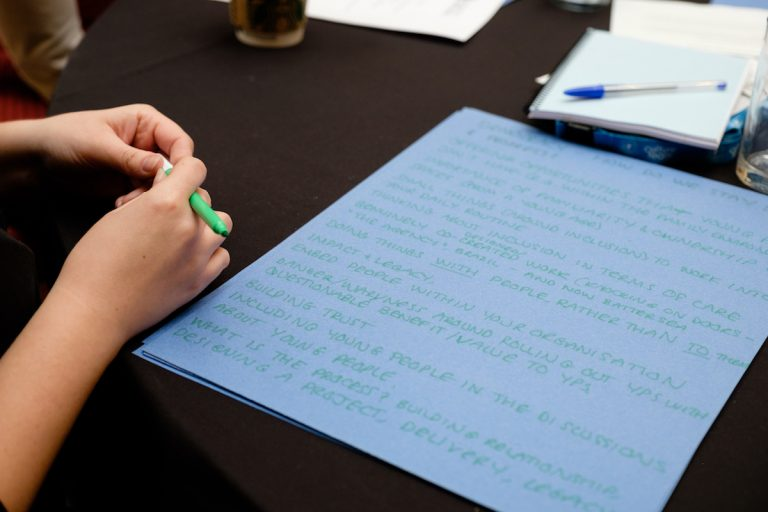 An over-the-shoulder photo of a hand, holding a pen, poised to write - with blue paper on the table, already filled with hand written notes.