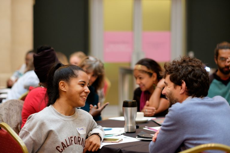 A group of people in discussion sat around a conference table, in the foreground, a younger girl and a man are smiling.