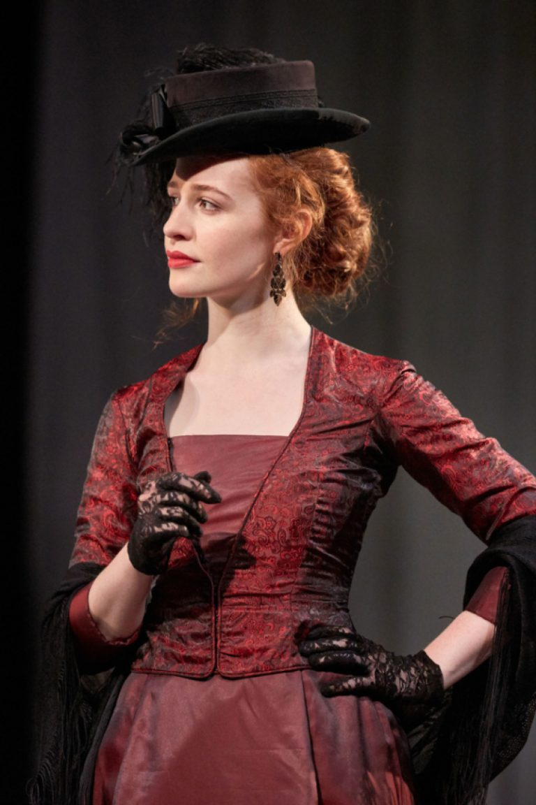 Bristol Old Vic Theatre School actress Grainne Mahony plays Mrs Kendall in The Elephant Man - a red-haired girl wearing a corseted red dress, black lace gloves and a hat.