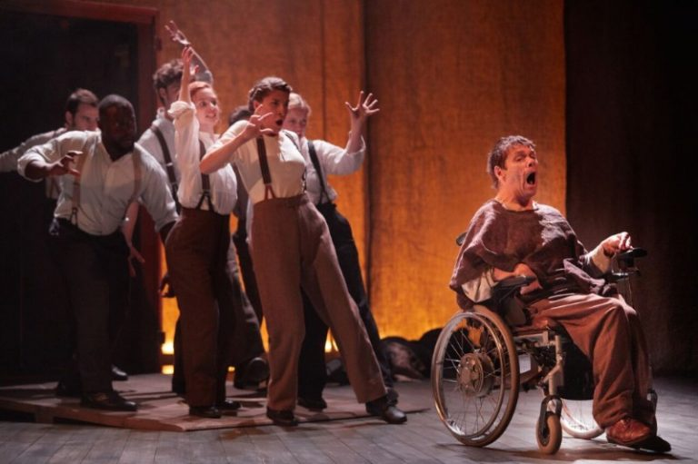 The Elephant Man, production photo: Jamie Beddard as Joseph Merrick, sits in whis wheelchair facing front of stage, an expression of horror and dismay on his face. The remaining cast of 7 actors are behind him, glaring, shouting and grabbing arms extended.