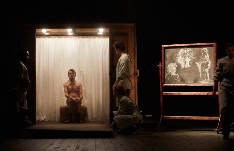 The Elephant Man, production image: Jamie Beddard as Joseph Merrick, sits wearing only shorts in a small wooden crate. A white curtain is behind and bright spotlights above eerily illuminate him. Other actors look to Merrick, wearing hospital aprons. A chalkboard to the right is illuminated, with anatomical drawings of the 'elephant man'.