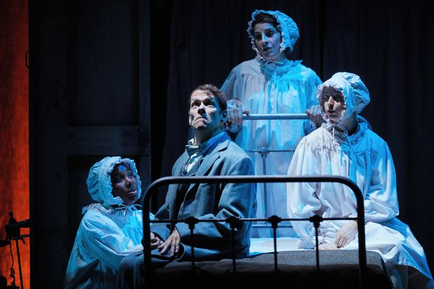 The Elephant Man, production image, Bristol Old Vic: Jamie Beddard as Merrick sits on an old bed, with Bristol Old Vic Theatre School cast (Liyah Summers-Madeleine Schofield and Stephanie-Booth) sat around him in white bedclothes and hats.