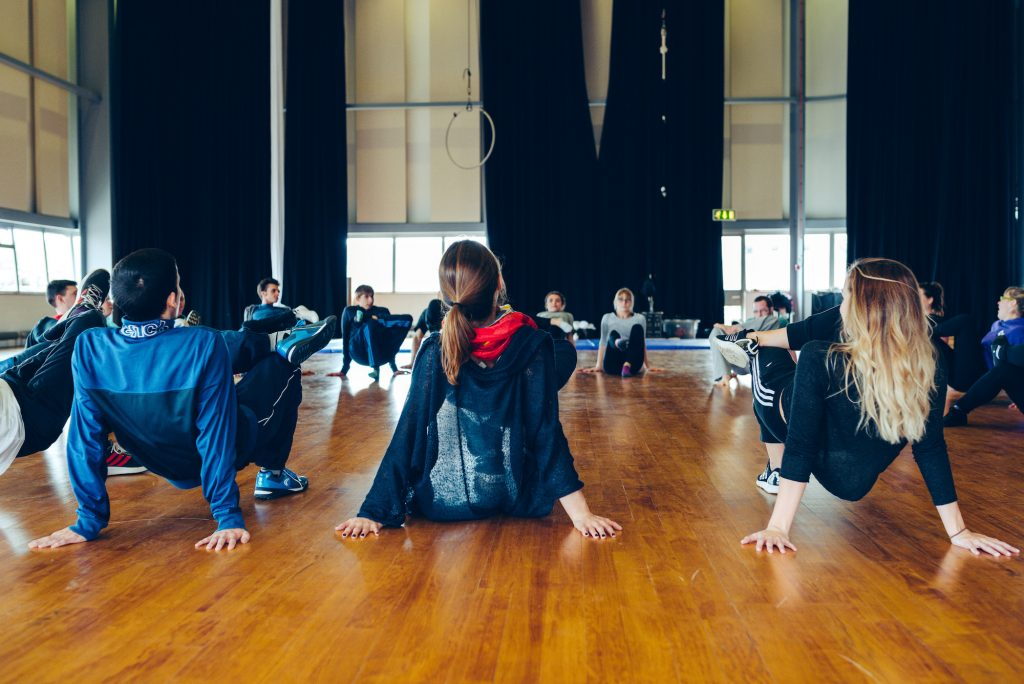 A group of workshop participants sat in a circle, with hands reaching behind their back, palms to the floor - one leg is ontop of the other knee. It looks like a good warm up stretch!