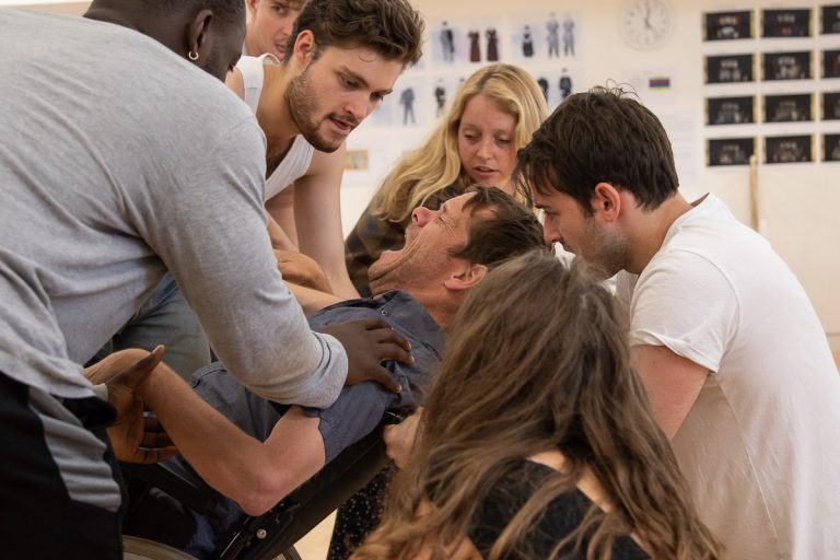 In the rehearsal room: Jamie is in the centre of the group in his wheelchair, with a distressed expression on his face. The other actors crowd closely around him are pushing their hands against him, pinning him into his wheelchair.
