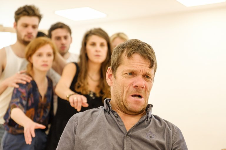 In the rehearsal room: Jamie is in the foreground, a distressed and concerned expression on his face. The actors gathered behind him are reaching forward, pointing at him with stern and serious facial expressions.