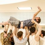 In the rehearsal room: BOV Theatre School students have lifted Jamie above their heads, arms outstretched. Jamie lays back, with his arms in the air, eyes closed, mouth is shouting.