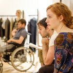 In the rehearsal room: Jamie sits in his wheelchair in the background, a young brunette man sits in the foreground with head in hands. A ginger girl sits in the foreground with a distant look on her face.