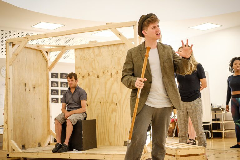 In the rehearsal room: Jamie sits in the background on a box, a BOV Theatre School student wearing a trilby hat and holding a wooden cane.