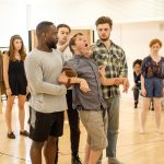 In the rehearsal room: Jamie is walking with two BOV Theatre Students either side of him, they are supporting his arms. Another student is behind, holding Jamie's chin and forehead, as if making him look up at something.