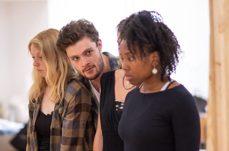 In the rehearsal room: A white brunette actor, his head over other's shoulders, glares across the room at a black actress. The girls have a sad expression.
