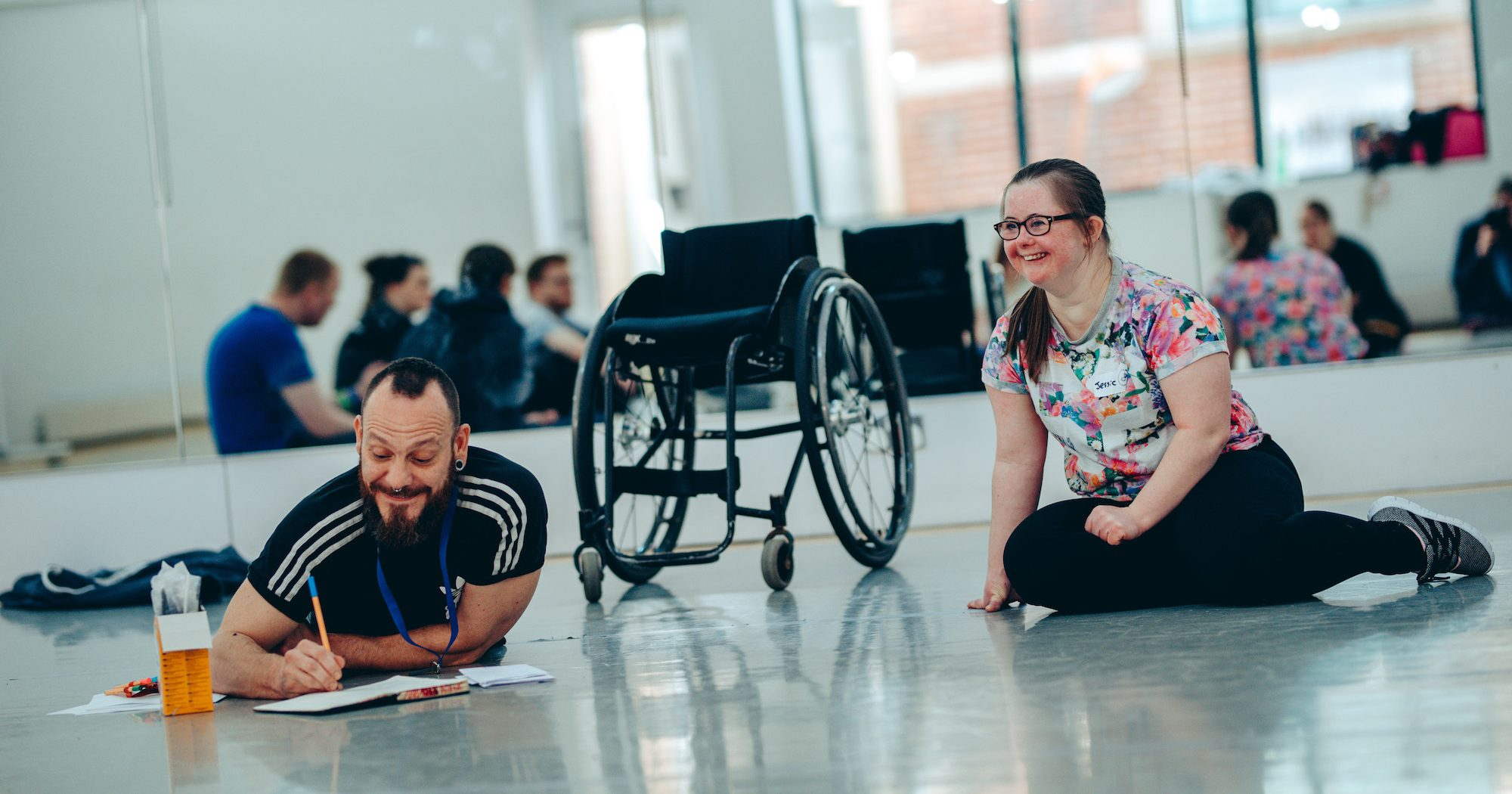 Daryl lays on the floor writing notes and smiling. A wheelchair is behind him. Jess sits next to Daryl smiling. Behind them is a large mirror - the reflection shows a group of people in the background.