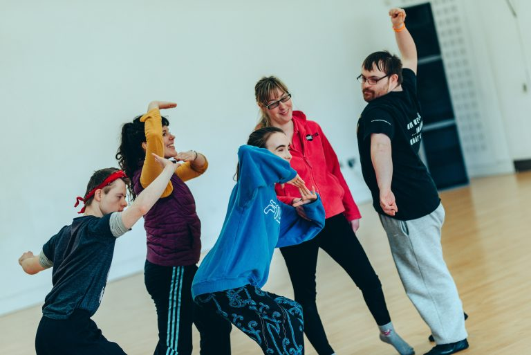 A group of 5 young workshop participants move around a studio space; they are lunging, stretching, twisting, reaching and smiling.