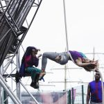 Extraordinary Bodies, What Am I Worth? performance shot from Sunderland 2018: Alfa performs her aerial rope moves, captured here suspended from the large aerial structure, her legs and arms extended in a backbend, entwined in the rope.