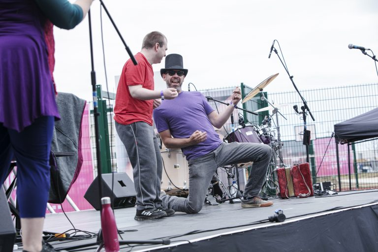 Extraordinary Bodies, What Am I Worth? performance shot from Sunderland 2018: The community cast members dance on stage; a man in a top hat and a bright purple top plays air guitar and laughs to the camera.