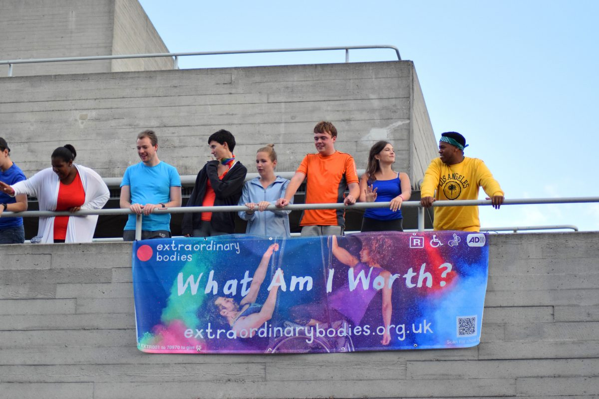 The community choir watch on and sing from the balcony above the stage - their colourful clothes are bright and empowering on the grey backdrop. They stand above the 'what am i worth' banner.