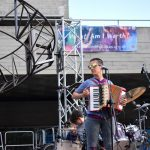 Amelia, wearing bright sunglasses, plays the accordion at the front of stage.