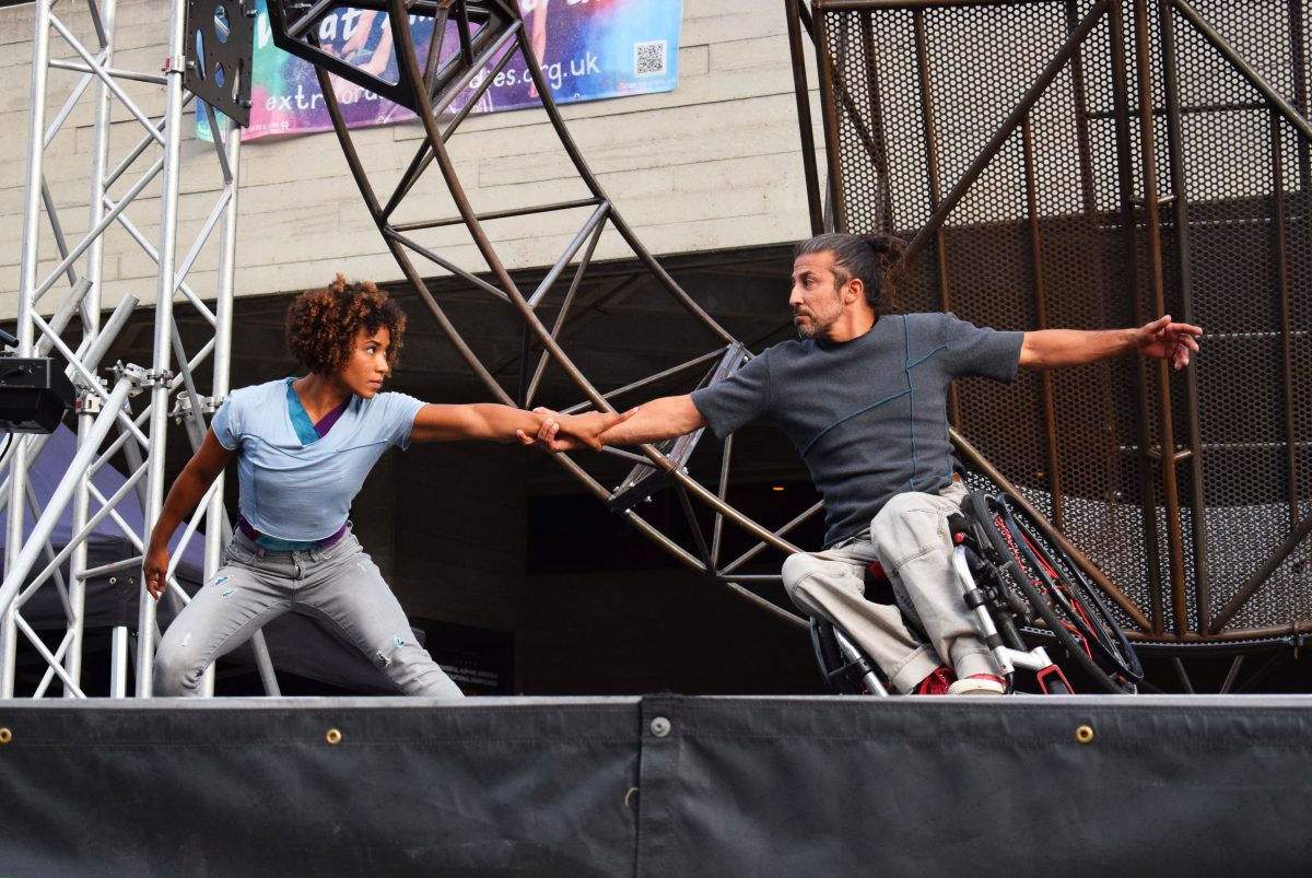 Alfa and Dergin are centre stage, arms grasped together, Alfa lunges towards Dergin, who leans on his wheelchair, balancing in the middle of their dance duet.