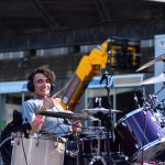 Jonny smiles to camera - he's on stage at his purple drum kit, spinning the drum sticks
