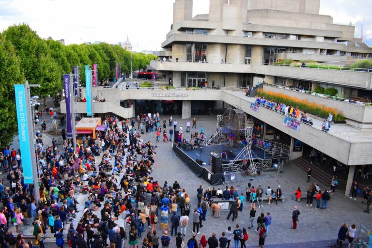 The large crowd watch the Extraordinary Bodies show 'What Am I Worth?' outside the National Theatre in London - as part of RiverStage Festival 2018.