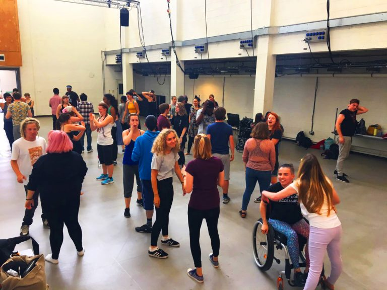 A large group of young artists from EBYA and National Youth Theatre gather in a large studio space. They are standing and exchanging conversations, everyone looks happy, laughing, smiling.