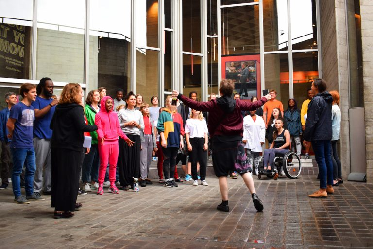 A diverse choir rehearse in front of the National Theatre, London.