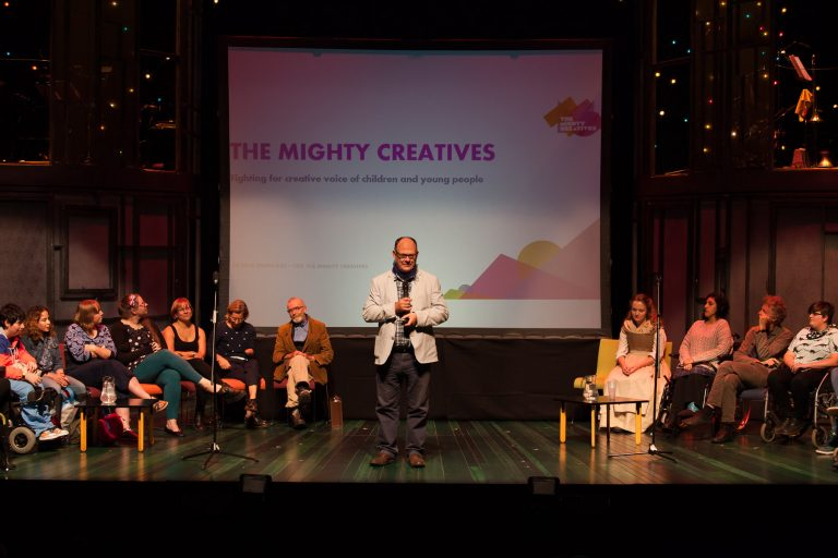 Nick Owen, standing centre stage, presentation behind reads 'The Mighty Creatives'. 12 others sit in a semi circle around Nick.