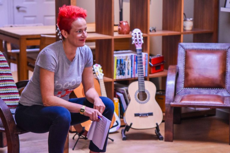 Sheila, the show Writer, sitting down with a smile on her face and a notepad in her hands, listening to someone speaking. She has red short hair.