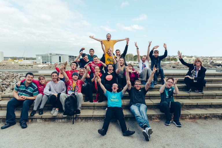A group of young artists outdoors waving a smiling under a blue sky