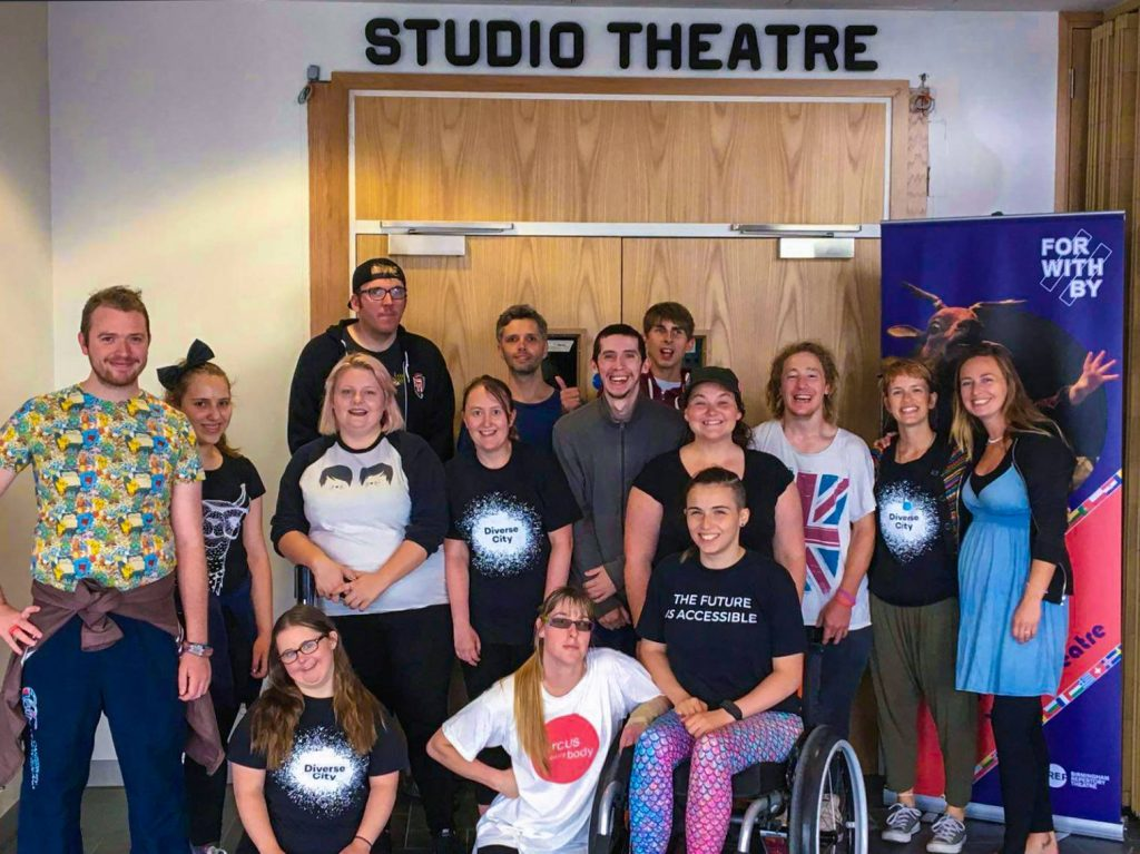 "A group of young artists standing together in a rehearsal space with a sign reading ""Studio Theatre"", all smiling"