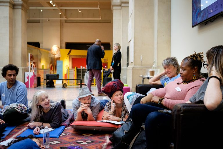 A diverse group of people gathered around sofa and rugs in the grand space at Bristol Museum. The group is deep in conversation.