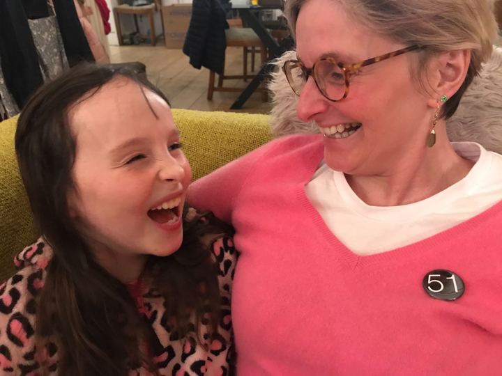Claire Hodgson sits on the sofa with her young daughter, Scarlett. They are both laughing in an embrace. Claire wears a badge that says '51' - representing 51% of the female population.