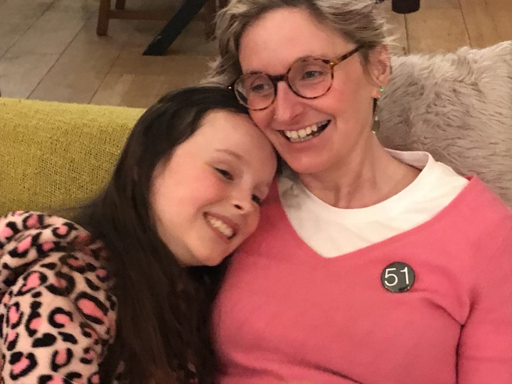 Claire Hodgson sits on the sofa with her young daughter, Scarlett. They are both smiling and hugging. Claire wears a badge that says '51' - representing 51% of the female population.