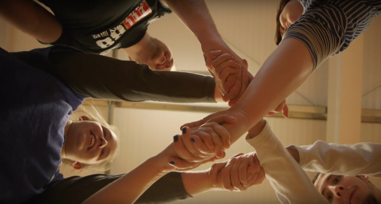 A group of young people clasp hands together - the camera is looking up between their hands to the ceiling - smiling faces are peeking between arms and hands.