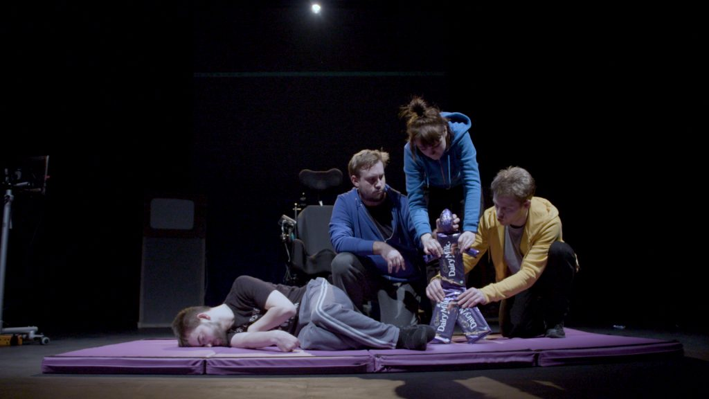 David Young lays down on a mat on the stage. Three actors are holding a 'chocolate puppet' - bars of Dairy Milk make up the body and an Easter egg makes the puppet head.
