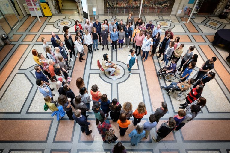 Doing Things Differently at Bristol Museum & Art Gallery. A diverse group of about 100 people are in a large circle in the grand entrance room to Bristol Museum. In the centre of the circle, a black man and black woman are leading the group through a movement exercise.