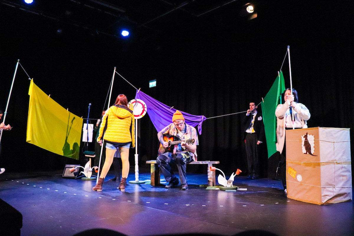 Extraordinary Bodies Young Artists perform Till We Win at Lighthouse Poole - a washing line with colourful sheets hangs across the stage. Keiran Proctor plays guitar on a bench.