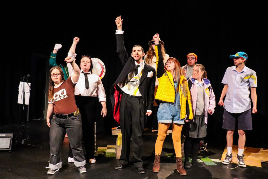 Extraordinary Bodies Young Artists perform Till We Win at Lighthouse Poole - the young company are on stage, gathered together, standing tall with fists punching high in the air.