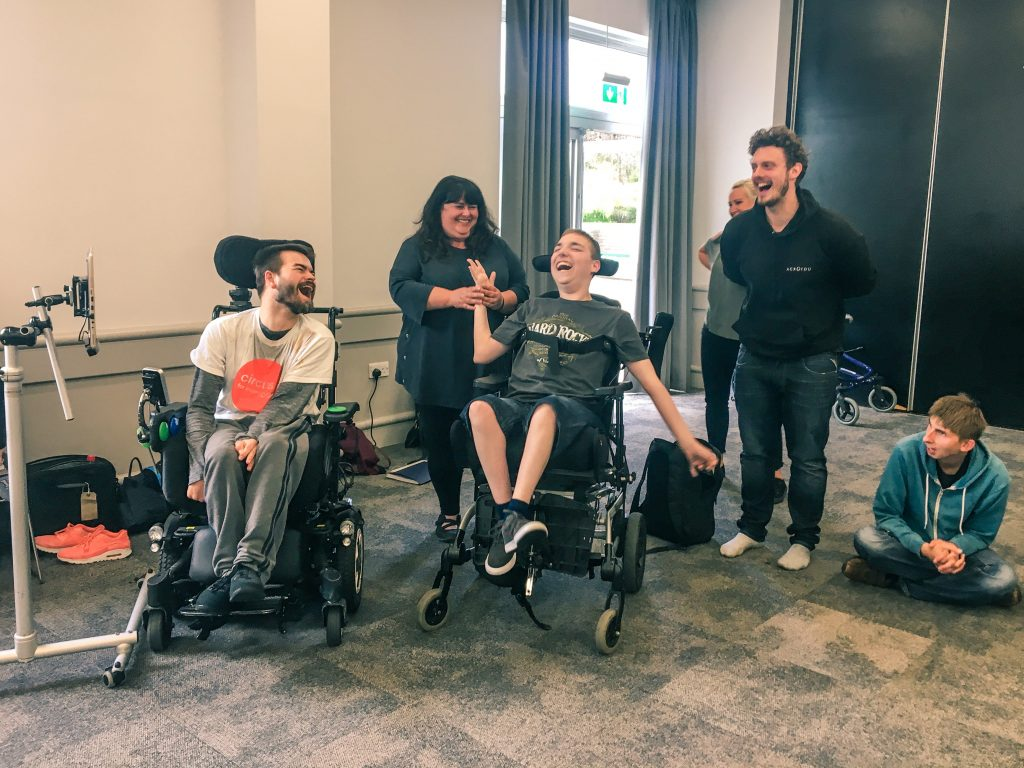 Two young men in electrical wheelchairs, a woman and two other men all laughing together, standing and sitting in a rehearsal space