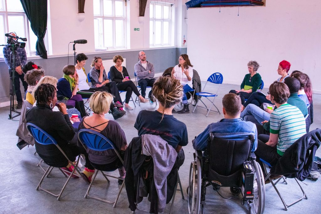A diverse group of people sitting on chairs in a circle. A woman wearing a white top and blue jeans speaks to them. In the background on the left, a man is recording the feedback session