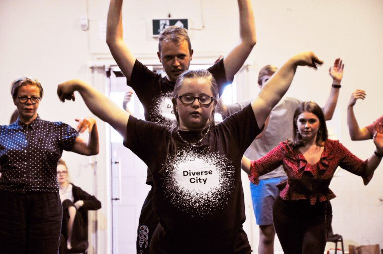 A young woman wearing glasses and a black t-shirt with a white Diverse City logo on it in the foreground. Her arms spread to her side, eyes closed. Behind her, several other performers making the same move.