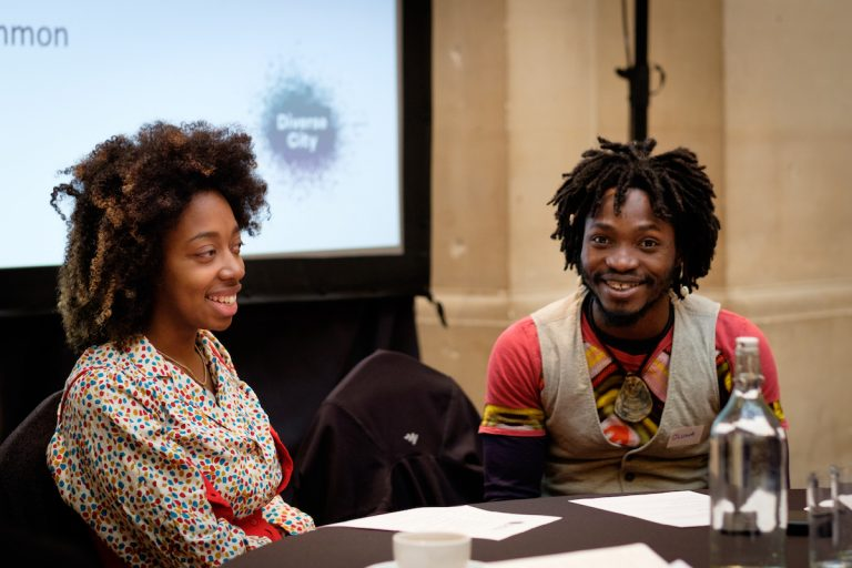 A young man of colour and a young woman of colour sit a table. In the background, a screen with a Diverse City logo