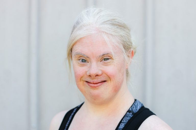 A young woman with Down syndrome poses for a portrait photo, her light blonde hair tied back. She has light blue eyes and wears a dark blue tank top.