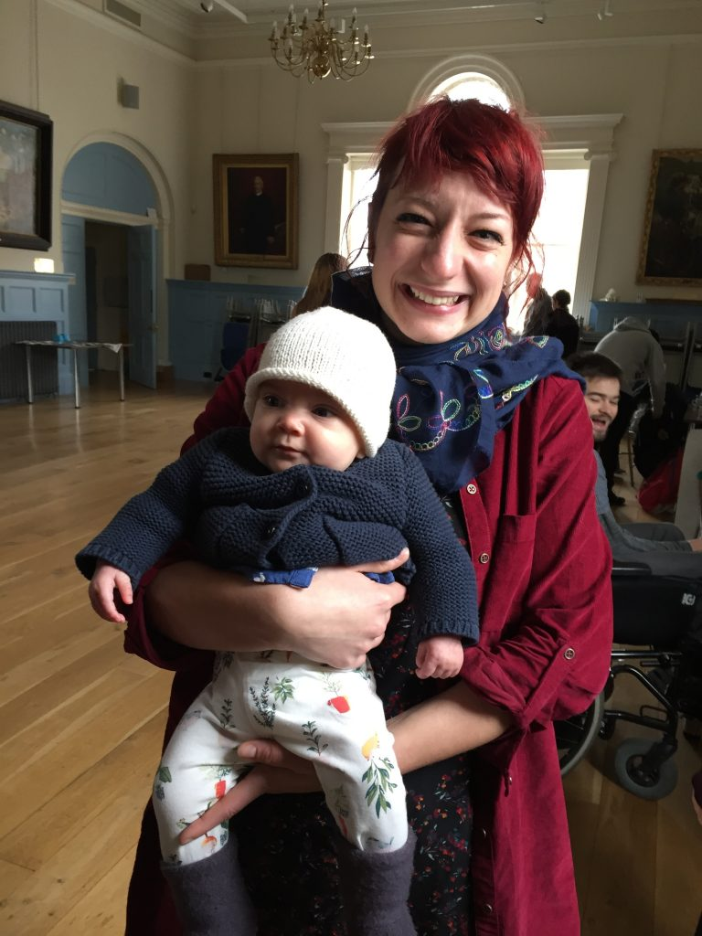 A smiling woman with red hair holds a baby with a white hat and dar blue jacket on inside an events venue.