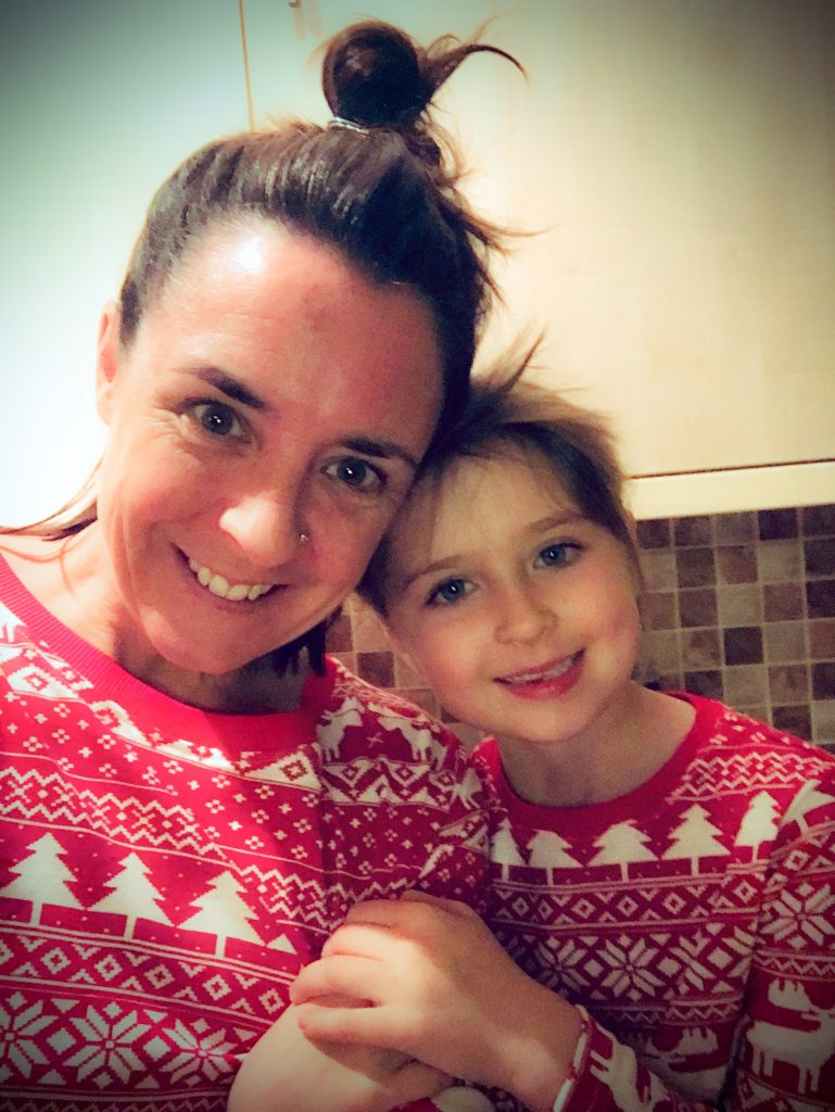 A woman with brown hair in a loose bun and a young girl with brown hair smile, both wearing red and white Christmas jumpers.