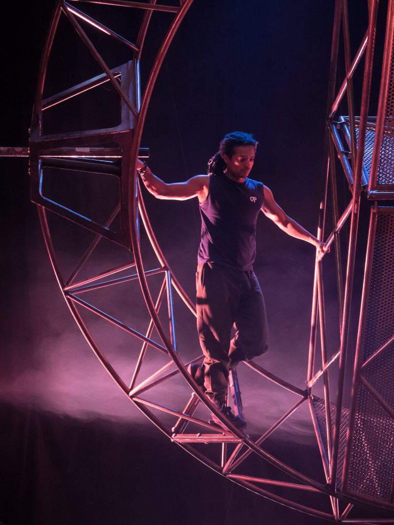 A man of colour with dreadlocks stands on a giant steel wheel, holding on to the bars.