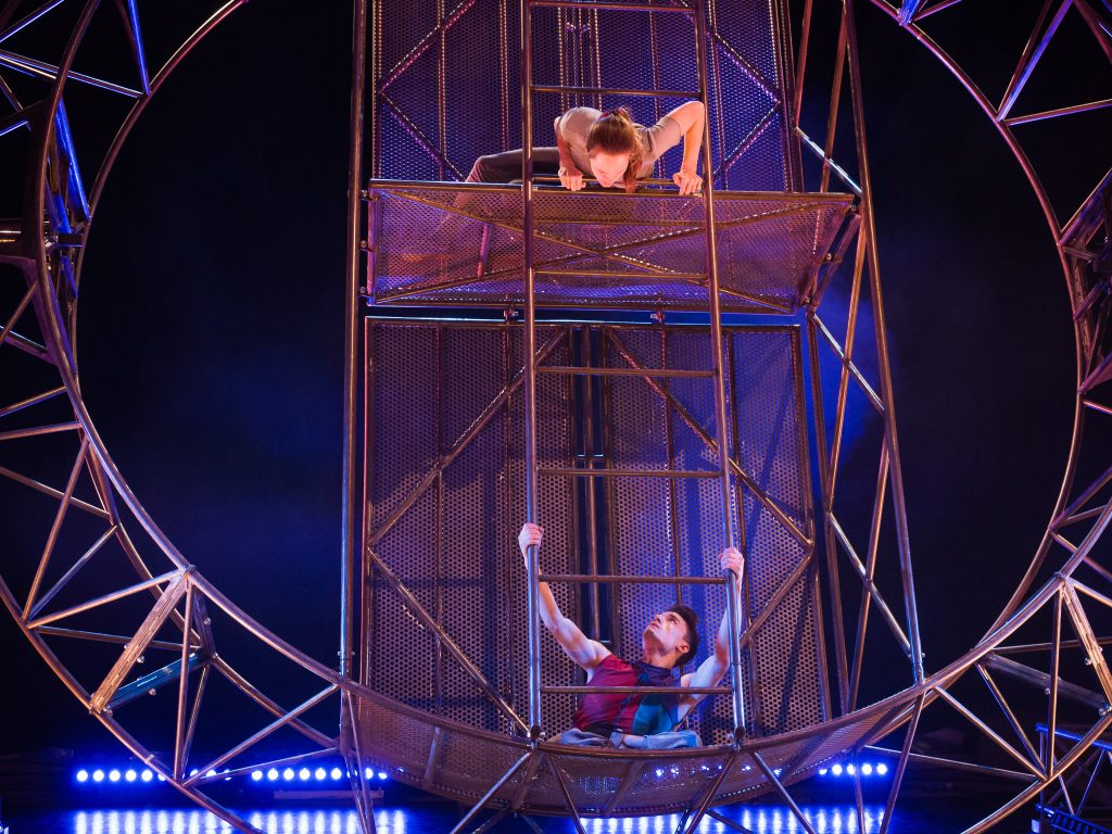 A woman and a disabled man look at one another, her at the top and him at the bottom of a giant steel wheel.