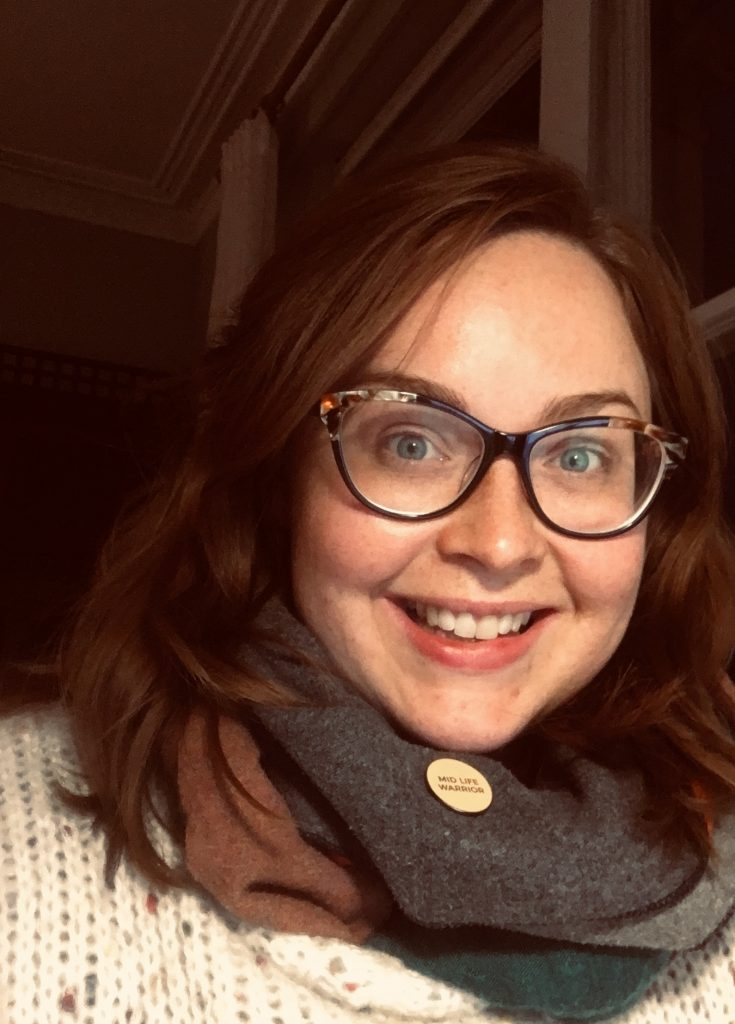 A woman with dark hair and glasses smiles at the camera, she is wearing a cosy wooden jumper.